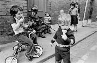 Enfants qui mangent des glaces pendant que les soldats patrouillent dans les rues. Londonderry, Irlande du Nord, 1979. Peter Marlow- Magnum